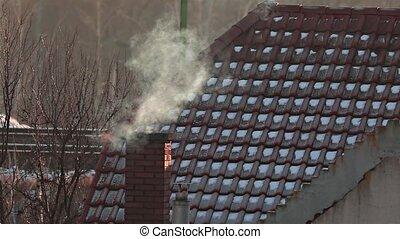 Smoking Chimney on a Roof - Smoking chimney slow motion from...