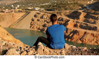 A man rests on a flooded quarry