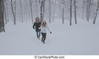 happy young couple run in winter garden