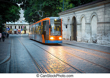 Tram on european city street at night