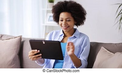happy afro american woman with tablet pc at home -...