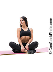 Vertical shot of fitness woman relaxing on mat - Vertical...