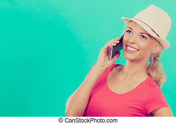 Tourist woman with sun hat talking on phone