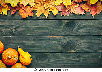 Autumn leaves and pumpkins over old wooden background with...