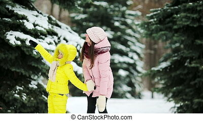 Mom and girl playing snowballs outdoors - Happy family...