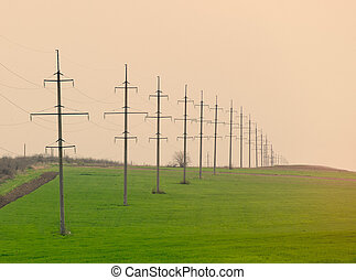 photo of high voltage power lines on the beautiful green field