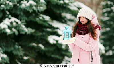 Young woman holding candlelight to warm her hands outdoors -...