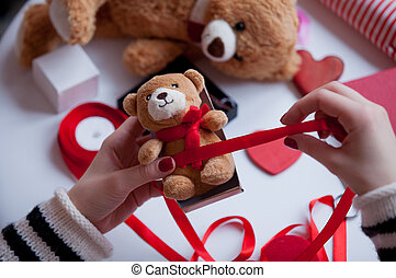 white caucasian hands wrapping teddy bear on the wonderful...