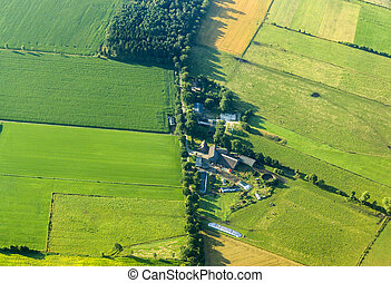 aerial view of green fields and farm house