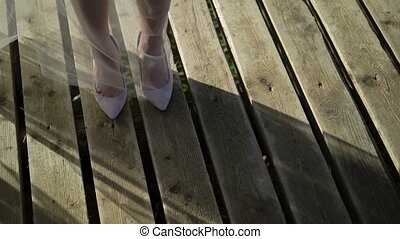 Bride staying on wooden desk in shoes and veil pan closeup