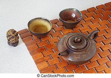 Tea set on a wooden substrate made of bamboo. Clay teapot...