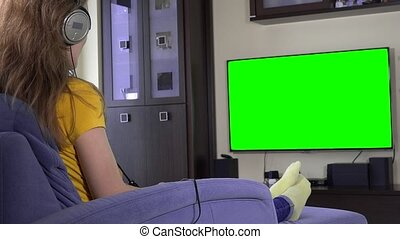 Woman with huge headphones have fun watching tv. Green chroma key screen