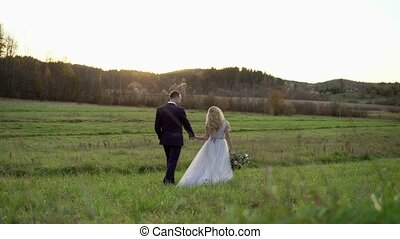 Wedding couple walking in a field at sunset
