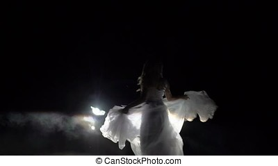 Bride in wedding dress dancing at night on a road