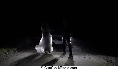 Bride and groom dancing at night on a road