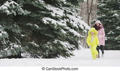 Young mother and playing snowballs outdoors
