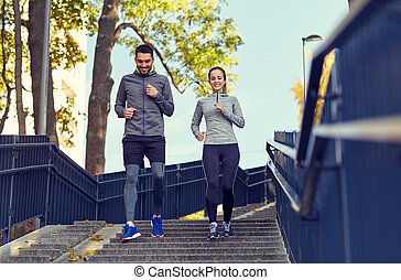 happy couple running downstairs in city - fitness, sport,...