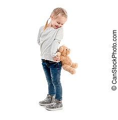 Girl peaking on a teddy, isolated