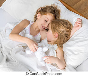two little sisters hugging in bed - two cute little sisters...