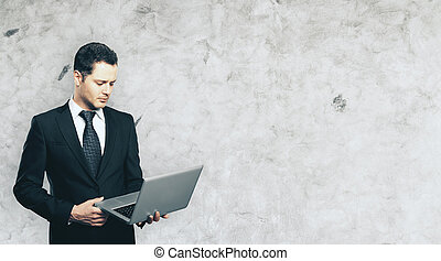 Businessman using laptop - Handsome young businessman using...
