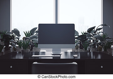 Backlit workplace with blank computer screen and decorative...