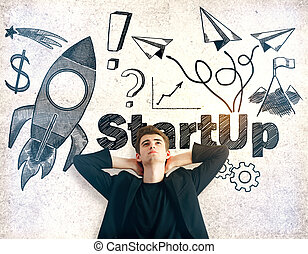 Startup concept - Relaxing young man on textured concrete...