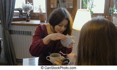 Young girls drink tea, have fun talking. Telling stories
