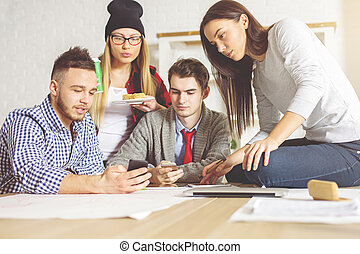 People checking smartphones - Young people in office taking...