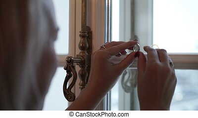 Young woman preparing wedding rings for shooting indoors