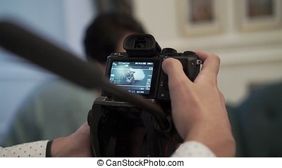 Man working with camera on tripod indoors shooting dog