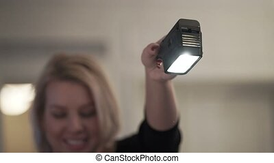 Young womah holding lamp for professional shooting photo or...