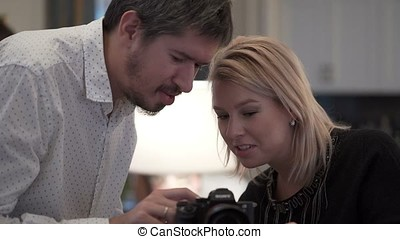 Man and woman working with camera on tripod indoors