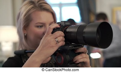 Young woman working with camera on monopod - Young woman...