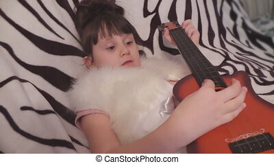 The girl is lying and playing a child's guitar