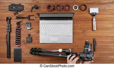 Hands male photographer removed camera from the tripod. Wooden table top view. Equipment for shooting on the table