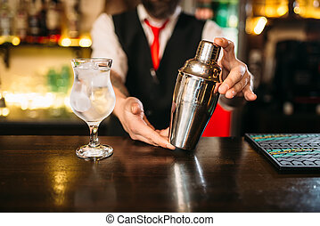Barman with shaker behind a bar counter with glass of...