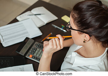 Young female bookkeeper considers on calculator - Young...