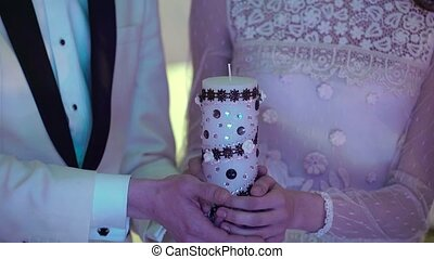 Bride and groom holding candle in hands