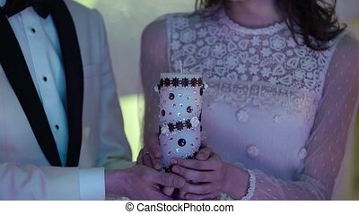 Bride and groom holding candle and light it - Bride and...