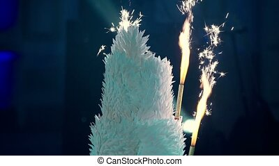 Beautiful white celebration cake with fireworks at the party
