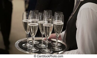 Waiter hold tray with glasses of champagne on event...