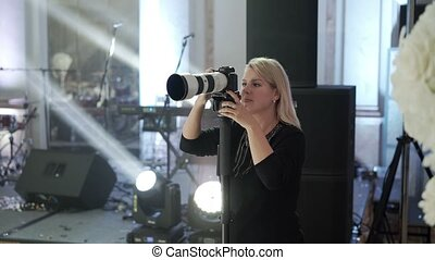 Young woman shooting photo and video on the party indoors