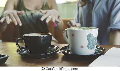 Two woman friends sharing coffee in cafe