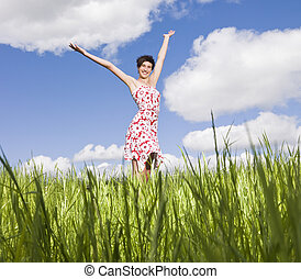 Young woman standing on a field with her arms raised