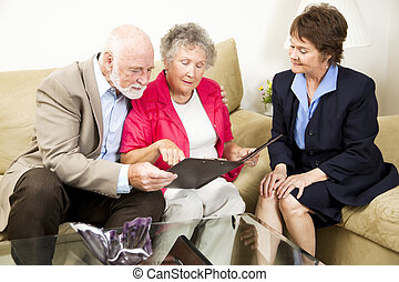 In Home Sales - Sales woman looks on as a senior couple...