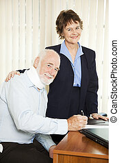 Injured Man with Lawyer - Injured senior man signing...