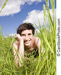 Smiling woman lying down in the grass