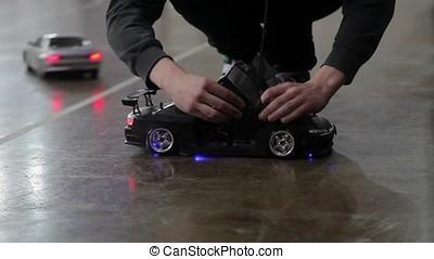 Man prepairing RC car for race indoors