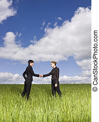 Two women standing in the grass shaking hands