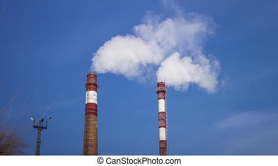 Steaming cooling towers and industrial chimneys, Smoking against the evening sky. pollution of atmosphere by emissions of harmful substances, environmental protection